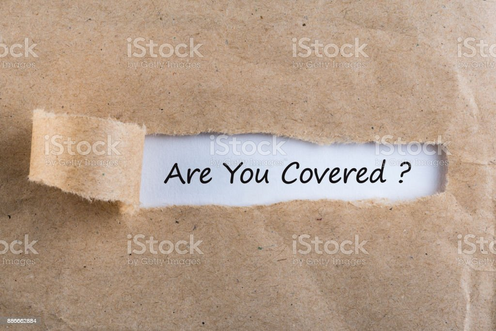 ARE YOU COVERED? Question message appearing behind ripped brown paper. Are you insured for your car, travel, home, health or other liability stock photo