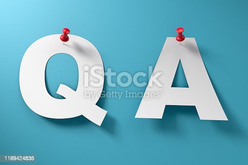 Questions and answers paper Q and A with red thumbtack pinned to blue paper background with no people.
