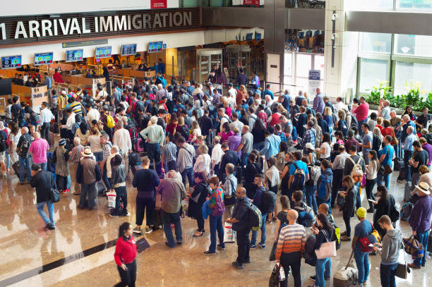 queue at airport immigration - emigration and immigration stock photos and pictures