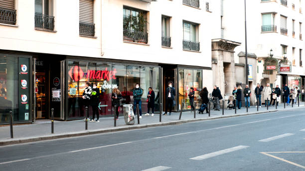 Queue in front of a supermarket during pandemic 2020 in Europe. Queue / one behind the other, in front of a supermarket during pandemic 2020 in Europe. People are waiting for run errands  Schools, bars, shops, restaurants, theatre... are closed. Everybody is confine at home, because of Coronavirus, but people can go out home to do food shopping.  Paris, in France. March 23, 2020 central europe stock pictures, royalty-free photos & images