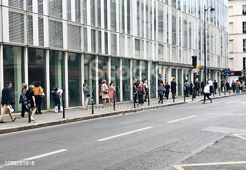 Queue / one behind the other, in front of La Poste during pandemic 2020 in Europe. People are waiting in the street. Paris, France - May 22, 2020.