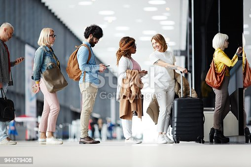Several passengers standing in queue while waiting for check-in registration before flight