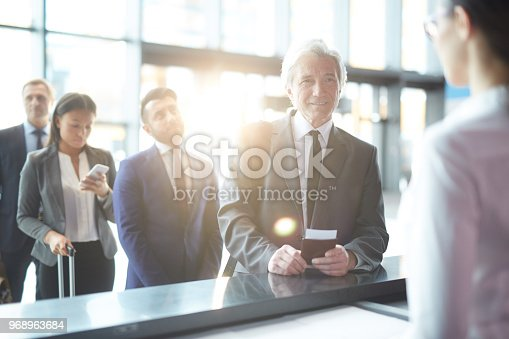 Senior businessman with passport and ticket standing by check-in counter in airport with queue behind