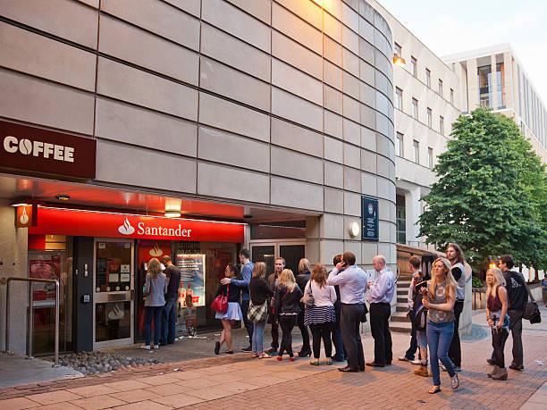Queue of people waiting at a Santander ATM; central Edinburgh