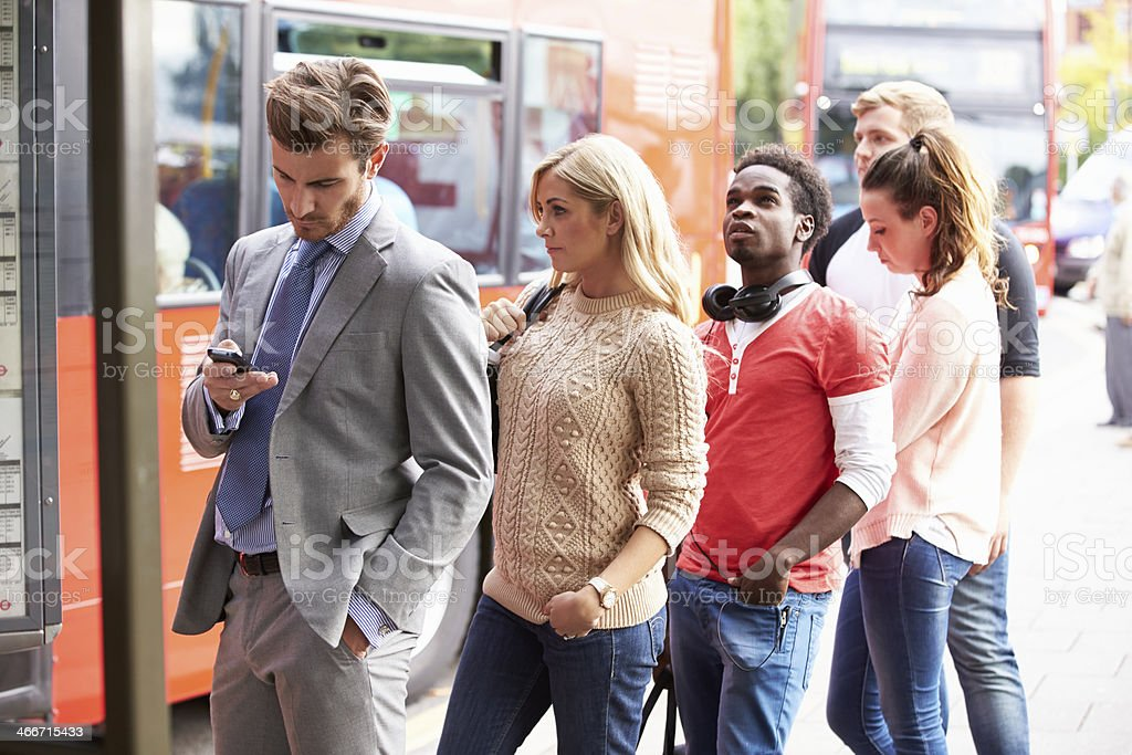 Queue Of People Waiting At Bus Stop stock photo