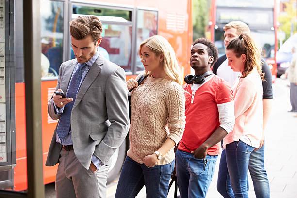 file d'attente de personnes qui attendent à l'arrêt de bus - queue photos et images de collection