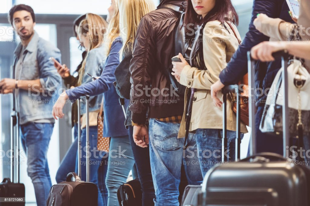 Queue of travelers waiting at boarding gate at airport stock photo