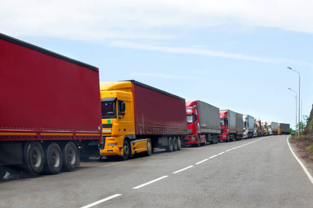 Queue of trucks passing the international border, red and different colors trucks in traffic jam on the road Queue of trucks passing the international border, red and different colors trucks in traffic jam on the road geographical border stock pictures, royalty-free photos & images