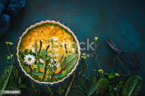 Quiche Lorraine savory tart vegan with raw vegetables creating a green garden on a dark green background