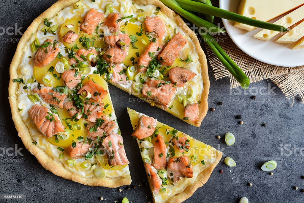 Quiche with salmon, cheese, sour cream, green onion and parsley stock photo