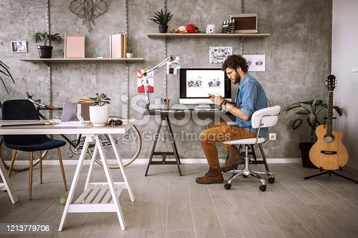 Young Man Working In Comfort of His Home, Sitting On Desk Taking Shorter Break To Text Some Messages