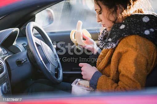 Young businesswoman is sitting in the driver's seat of her car eating a banana.