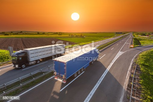 istock Quick delivery trucks on the empty highway at sunset 530192832