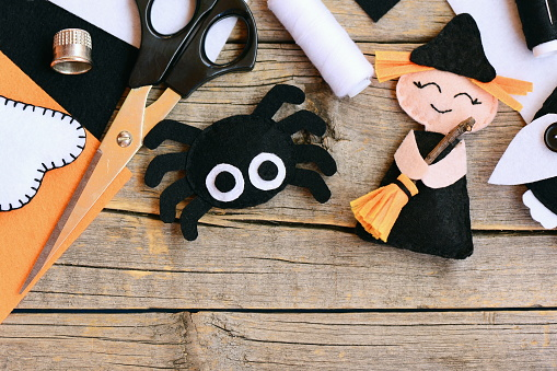 istock Quick Halloween crafts. Felt witch doll, spider decorations on a vintage wooden background. Needlework tools and materials. Easy felt Halloween crafts for preschoolers. Top view 841511586