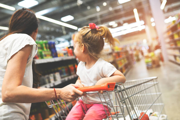 Eine schnelle Mutter mit einer Tochter in einem Supermarkt – Foto