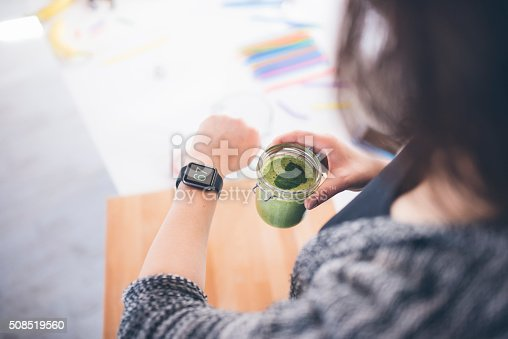 A close up of a young woman drinking her morning smoothie and checking her heartbeat