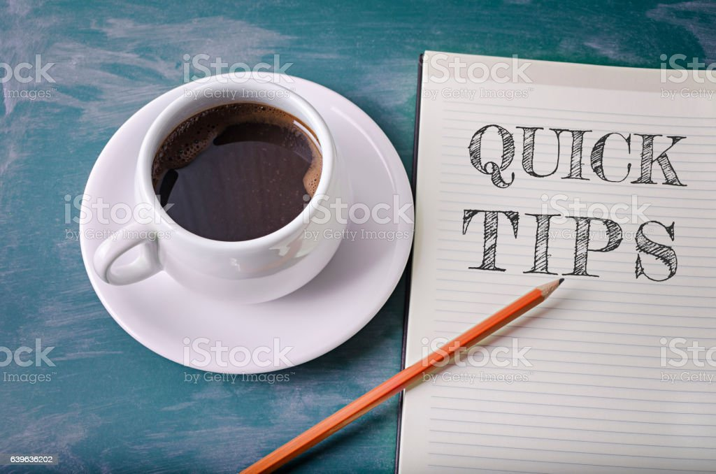 Quick tips text in a notebook with pencil and coffee stock photo