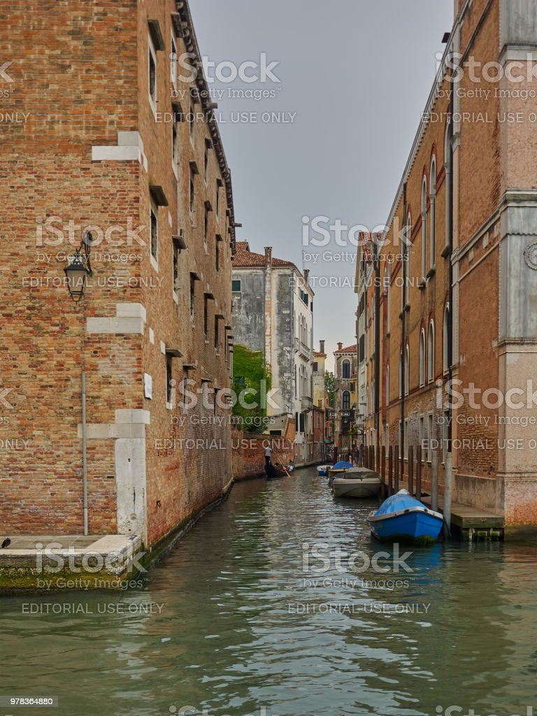 Quiet back canal with moored boats, Venice, Italy stock photo