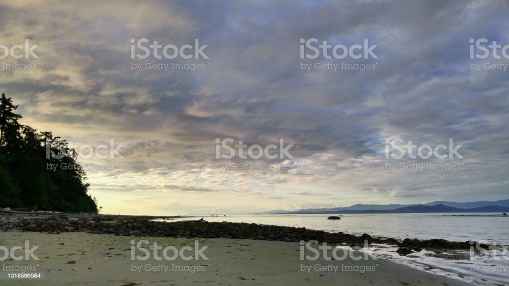 A quiet coastline at sunset, cloudy sky stock photo