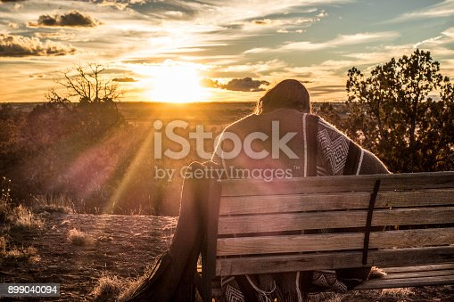 Woman playing guitar on a mesa in eastern Arizona at sunset. American Southwest.