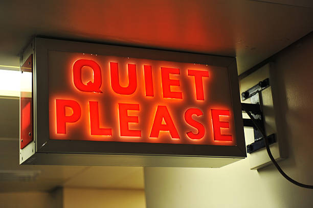 Quiet Please A vintage illuminated sign calling for quiet finger on lips stock pictures, royalty-free photos & images