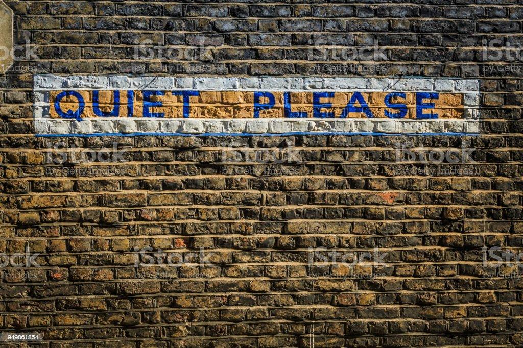 Tranquila por favor firmar en una pared de ladrillo - foto de stock
