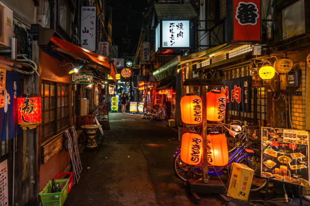 A quiet street in Osaka with traditional Japanese restaurants and lanterns stock photo