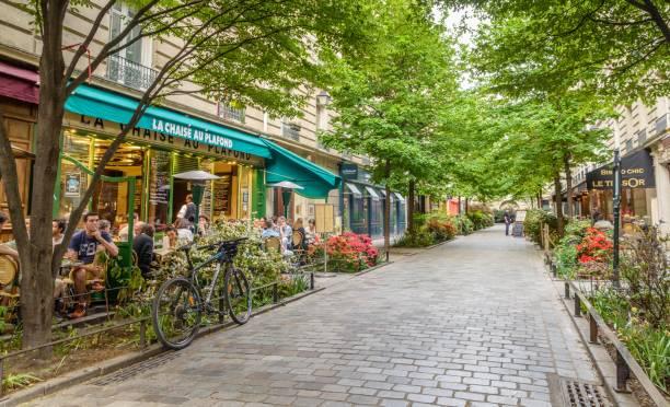 A quiet street with restaurants in the bohemian Marais district of Paris stock photo