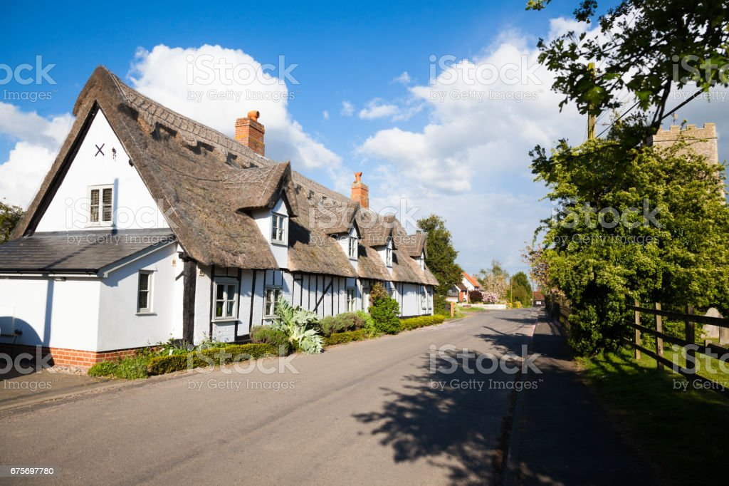 Quiet Suffolk quaint traditional village street Church and houses in spring sun with clouds royalty-free stock photo