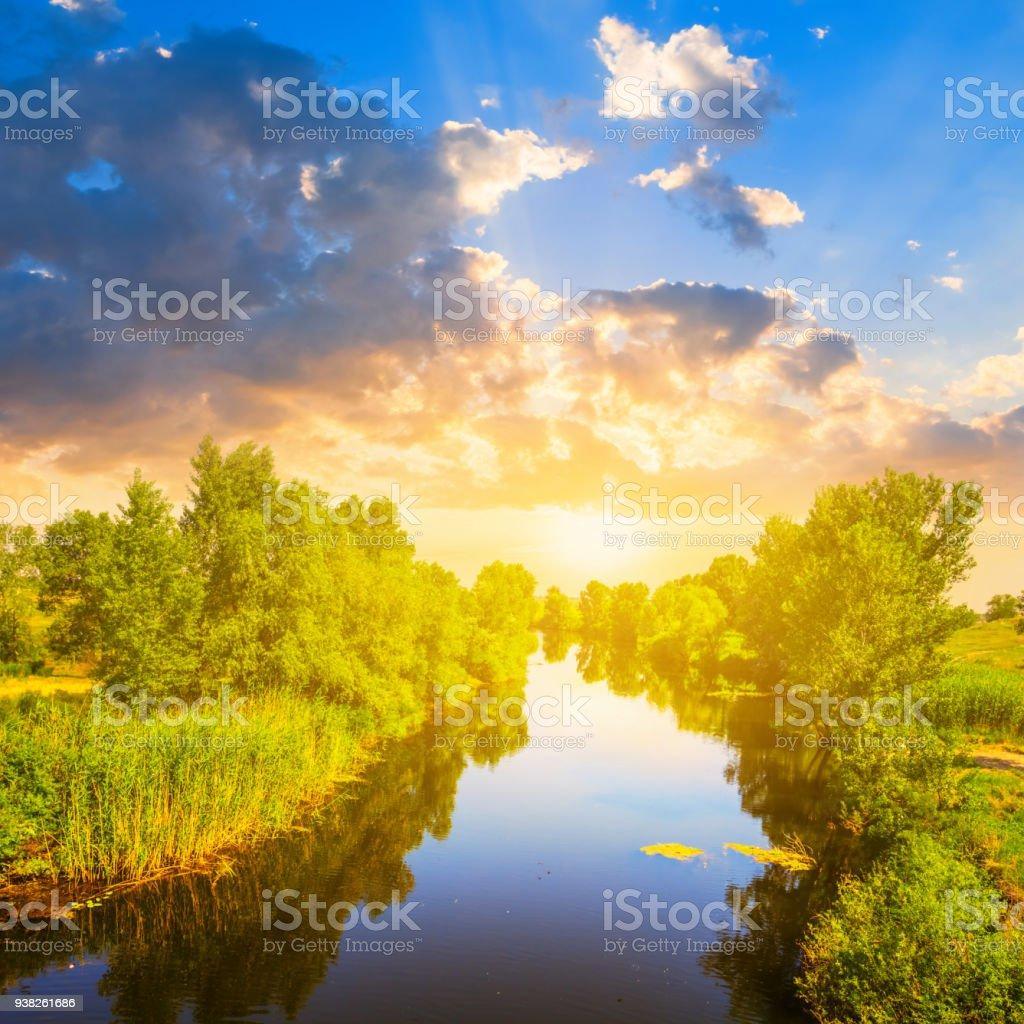 quiet summer river flow to a evening sun stock photo