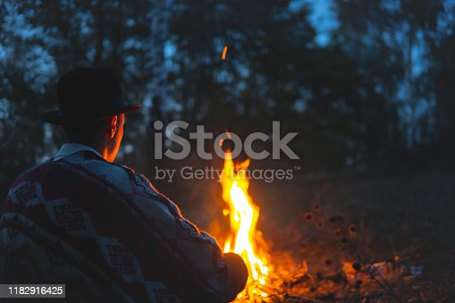 Man in poncho and hat sits by the fire in the wood