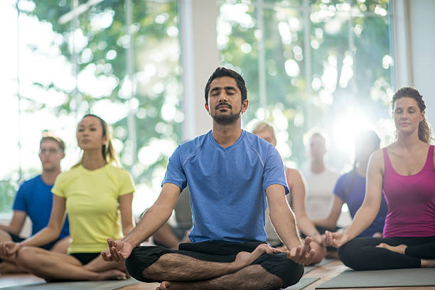 Quietly Meditating in Class A multi-ethnic group of young adults are taking a yoga class together at the gym. They are sitting on their mats and meditating with their eyes closed. yoga class stock pictures, royalty-free photos & images