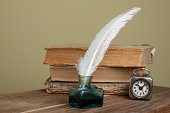 istock Quill and inkwell, old books, vintage clock on wooden table 177228055