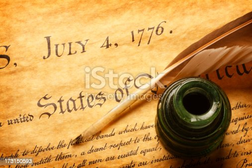 A feather quill and inkwell sitting on top of the American Declaration of Independence. The quill and inkwell sit next to the scribing of one of the most famous dates in world history, July 4, 1776.  A warm golden color scheme dominate the image.