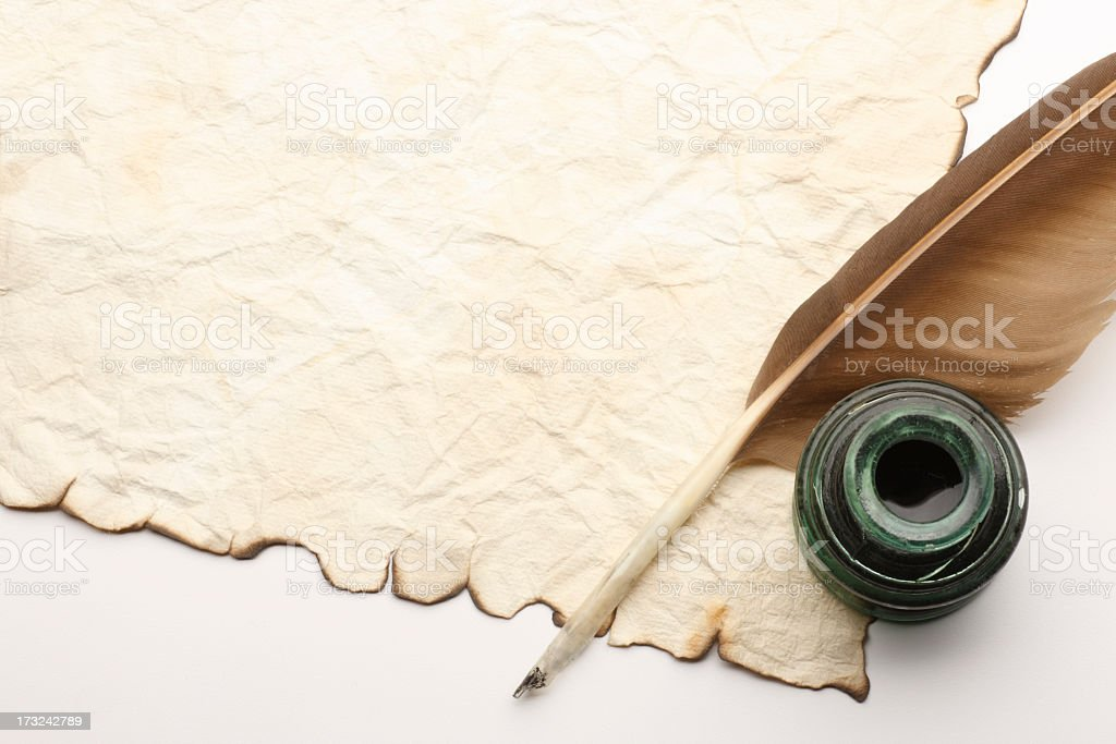 Quill and Inkwell on top of old blank document stock photo