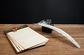 istock Quill ink pen and inkwell, old notebook on wooden table 148170862