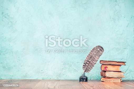 istock Quill ink pen with inkwell and aged books on wooden desk front aquamarine concrete wall background. Vintage old style filtered photography 1055440524