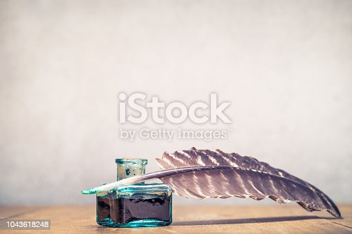 istock Quill ink pen with inkwell on wooden desk front concrete wall background. Vintage old style filtered photography 1043618248