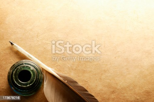 Feather quill and inkwell on rustic surface.