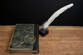 istock Quill, inkwell, antique book and magnifying glass on wooden table 177316901