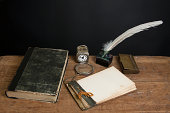 istock Quill, inkwell, book, magnifying glass, notepad, clock on table 177012518