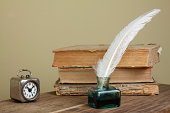 istock Quill, inkwell, old books, vintage clock on wooden table 177035885
