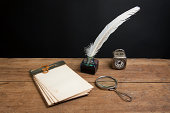 istock Quill, inkwell, old notepad, magnifying glass, clock on wood 177005310