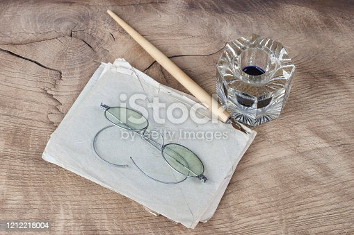 179239584 istock photo Quill pen and glass inkwell with old letters 1212218004