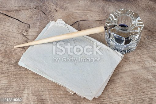 179239584 istock photo Quill pen and glass inkwell with old letters 1212218030
