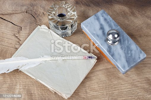 179239584 istock photo Quill pen and glass inkwell with old letters 1212218039