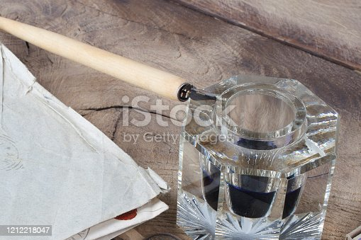 179239584 istock photo Quill pen and glass inkwell with old letters 1212218047
