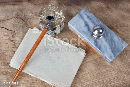 179239584 istock photo Quill pen and glass inkwell with old letters 1212218593