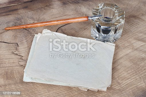 179239584 istock photo Quill pen and glass inkwell with old letters 1212218599
