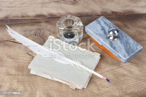 179239584 istock photo Quill pen and glass inkwell with old letters 1212218603